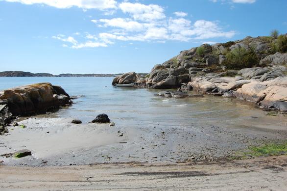"""Nur 100 m vom Haus liegt diese Bucht mit einem langen, herrlichen Sandstrand und den typisch rundgeschliffenen Bohus-Felsen. Hier lohnt sich vor Allem morgens und abends ein Besuch, da der Strand dann meist vollkommen unbesucht und traumhaft ruhig ist. Geniessen Sie hier z.B. eine Tasse Kaffee nach einem morgendlichen Spaziergang oder ein erfrischendes Bad nach einem abendlichen Workout. Der Weg hierher ist so kurz, dass man diesen schon strandfertig-bekleidet zurücklegen kann. Der Felsen """"hoppklippan"""" (Felsen der Hoffnung) hinter dem Ruderboot auf diesem Bild liegt schon in so tiefen Gewässern, dass selbst ein Boot mit mehr Tiefgang hier zeitweilig ankern kann."""