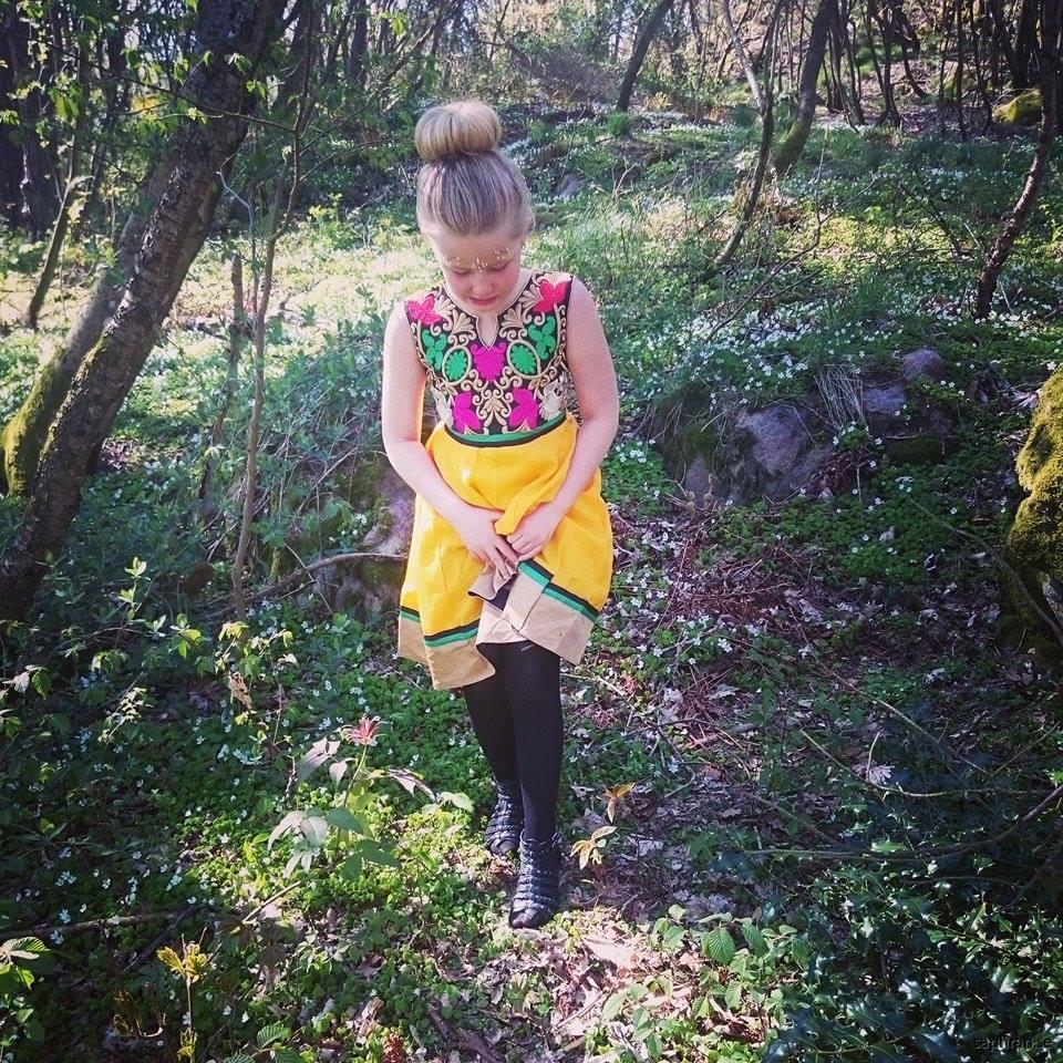 Mönstrad barnklänning i gult med skimrande broderat mönster.