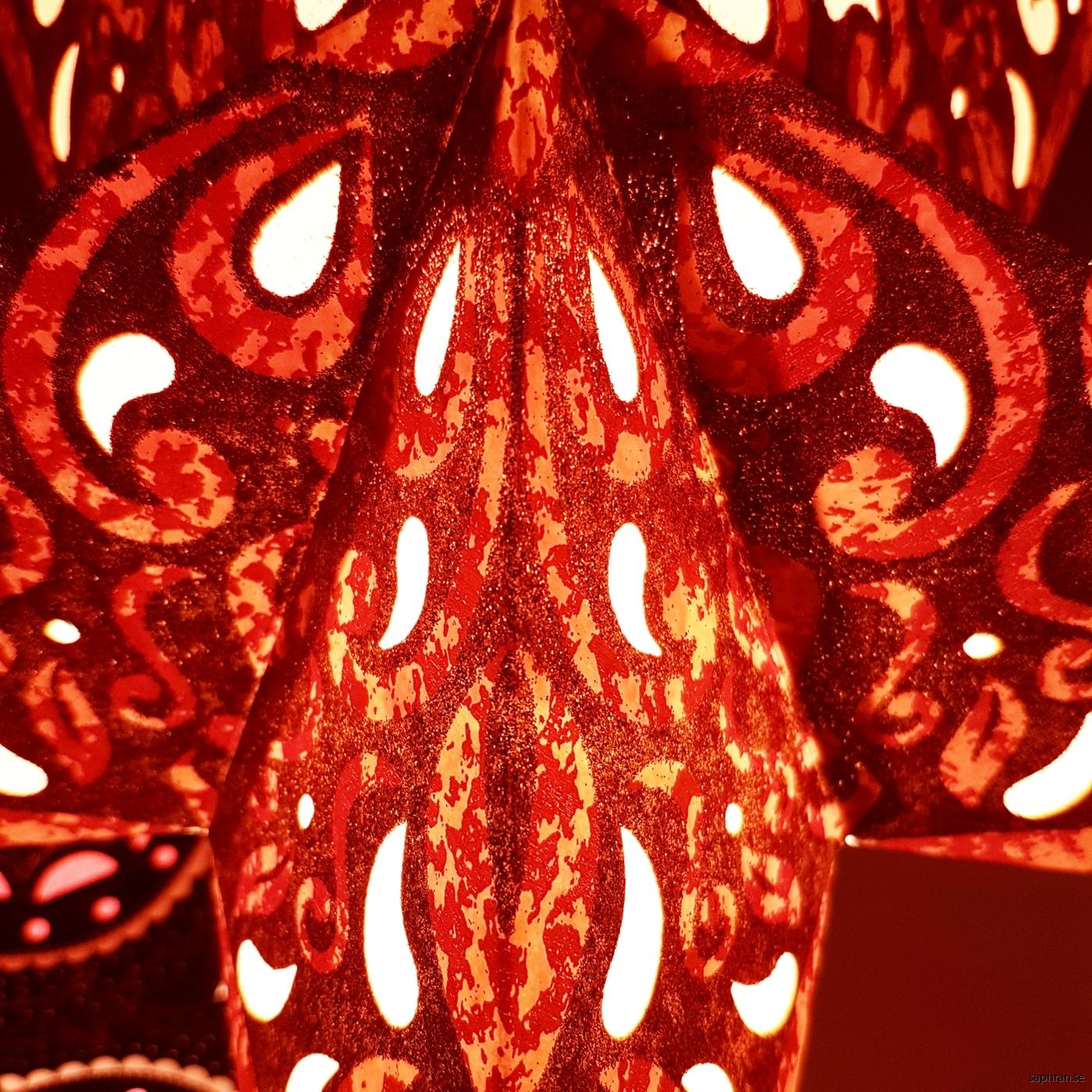 Guldglittrig adventsstjärna med mönster i rött och oranget