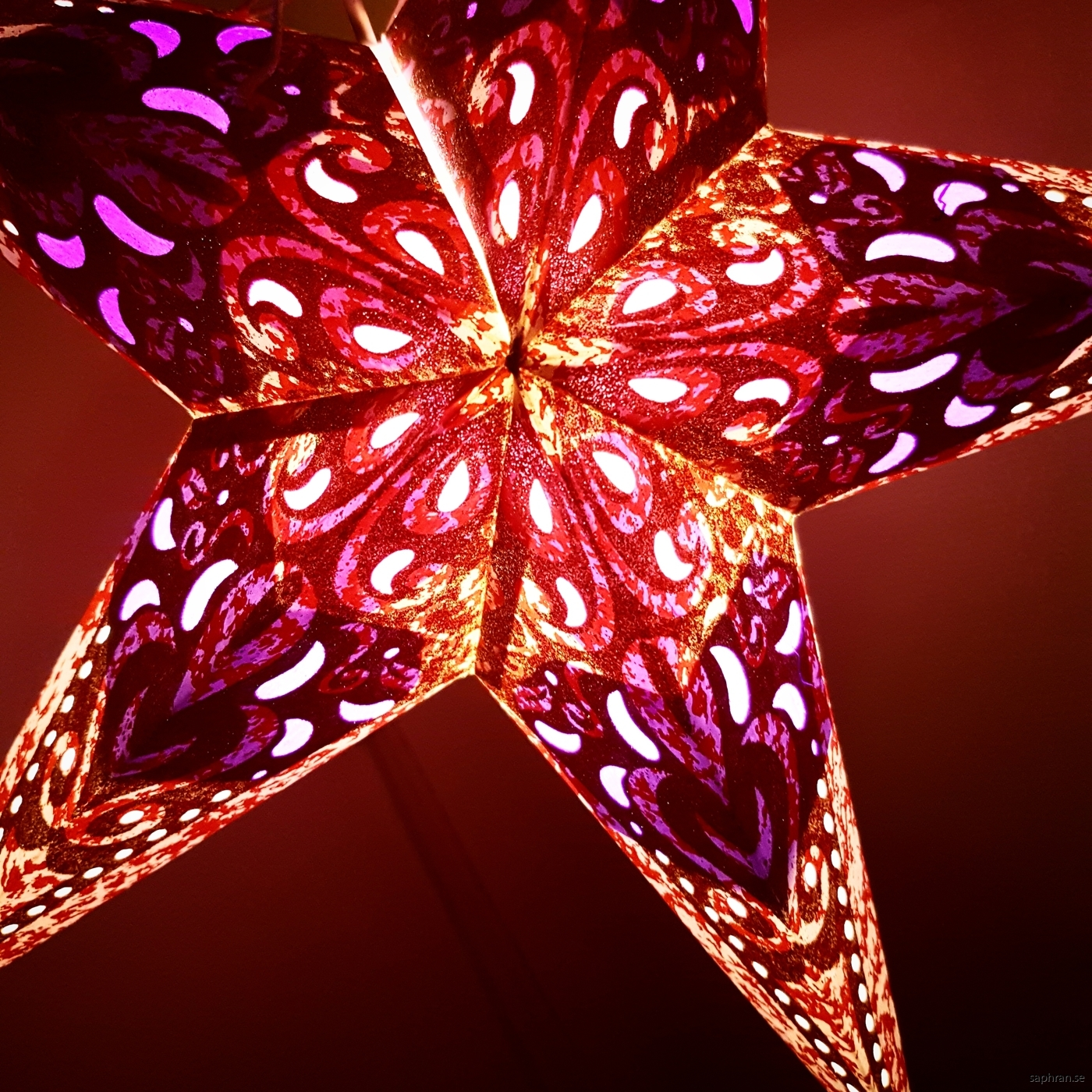 Färgglad, guldglittrig julstjärna i papper med lila detaljer