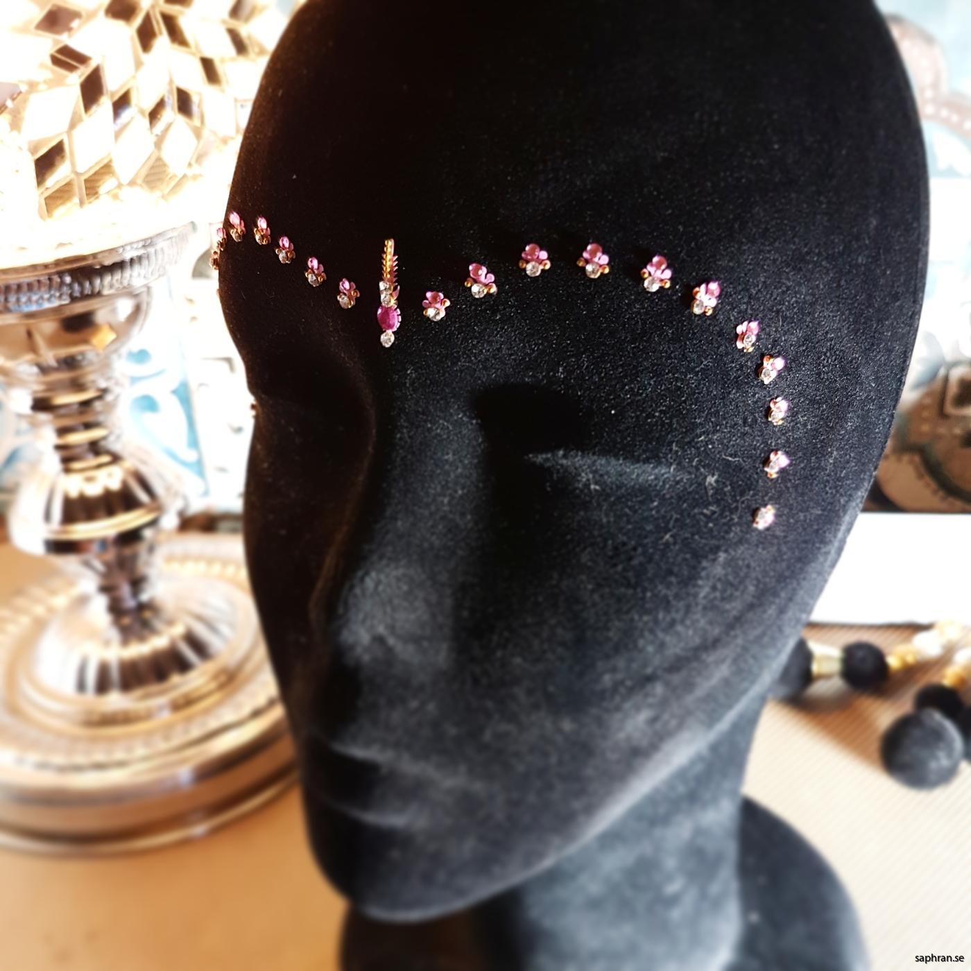Ett rosa orientaliskt smycke med silverdetaljer för fest