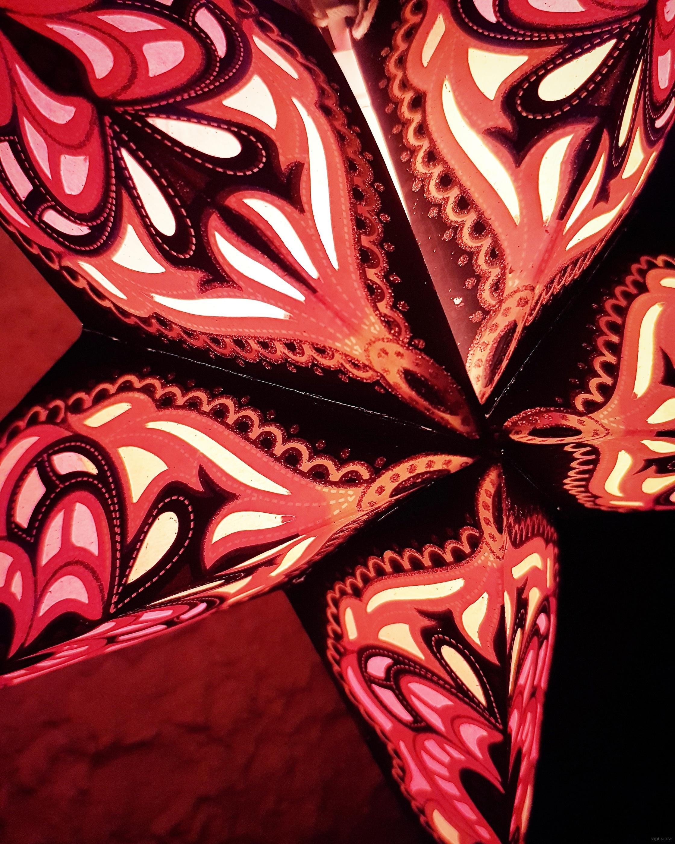 Guldglittrig adventsstjärna med mönster i svart och oranget