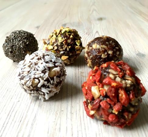 Rawbollar rullade i chiafrön, pistage, kokos och gojibär.