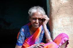 Gammal kvinna utanför sitt hus, södra Indien