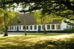 Norra Åsums prästgård med ramslök i trädgården och prästgårdsparken.