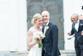 Brudbukett och Corsage med vackert brudpar i ett regn av ris. Vårbröllop i Varberg, Halland. Fotograf Nicole Henriksson