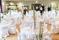 Bröllopsmiddag med höga bordsdekorationer med vita delphinium, rosor, rosblad.