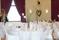 Höga bordsdekorationer i glasvaser i vita och rosa toner, till rundabord vid bröllopsmiddagen