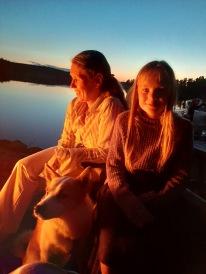 Nina och Linnea med Zingo i brasans sken.