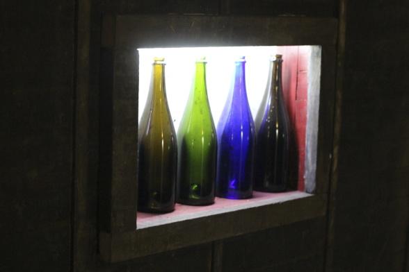 Champagneflaskor i regnbågens färger upplysta som dekoration i den nya vinkällaren.