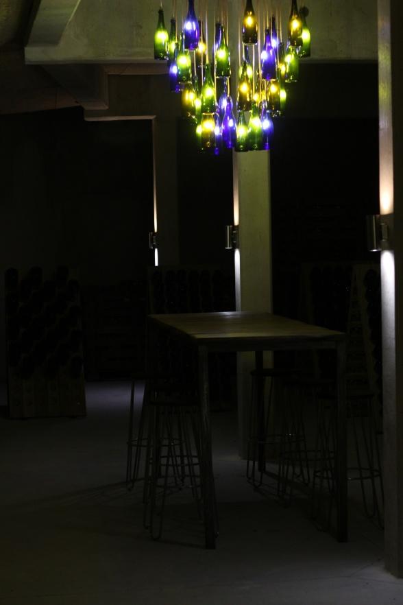 Snygg designad lampa med Champagne Mathelins egna flaskor inne i provrummet i vinkällaren.