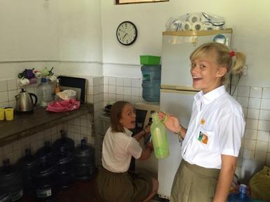 Maja och Stina i skolköket där de fyller på sina vattenflaskor.