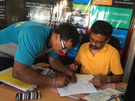 En koncentrerad Janaka plitar ner sin namnteckning för att vi ska få öppna ett bankkonto!
