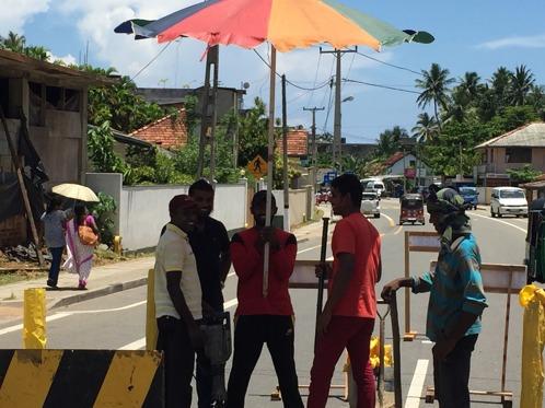 Vägarbete i Hikka, varav en person som bara håller i parasollen...