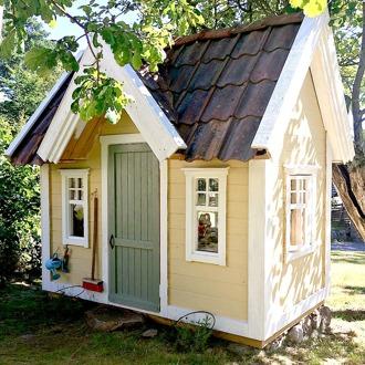 Lekstuga Bollstanäs, här med riktigt taktegel. Lekstugan har flaggfönster och är målad i gult. En lite mindre lekstuga, men lika söt leksuga för dig som inte har så mycket plats i trädgården.
