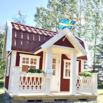 Lekstuga Saltängen. Här målad med falu rödfärg och med vit snickarglädje på altanräcken.