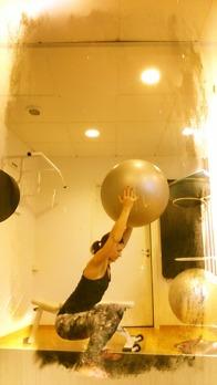 Strta stående med bollen neråt. Sätt dig ner i en knäböj och lyft armarna ovanför huvudet. Rakt linje ska då bildas från höftled och ut mot fingertopparna.