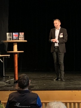 Micael Lindberg pratar på scenen i Ötersund i samband med SeniorExpo-20.