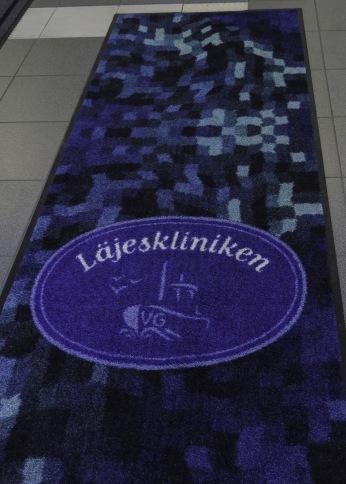 """Entrémattan """"Blå Nilen"""" i böljnde mönster med Läjesklinikens logo."""