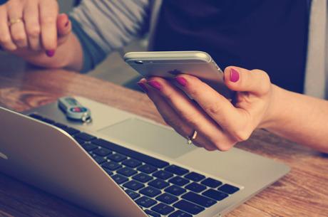 Arbetsplats, kvinna, dator och mobil