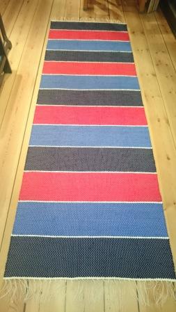 Bilden föreställer En matta i breda blockränder i mörkt blått/rött/ljusblått. Ett tunnt vitt inslag mellan ränderna. Tekniken är tuskaft