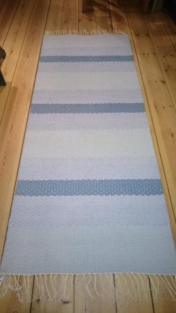 Bilden föreställer En grå/blå/lila matta i partier med olika strukturer