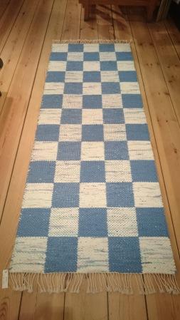 Bilden visar En rutig matta i blått och ljusblått/vitt. Tekniken heter dubbelväv och mönstret är tvärtom om man vänder på mattan.