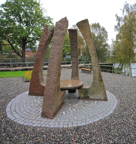 """Kanalparken vid övre slussen i Töcksfors med skulpturen """"Kraftsamlare"""" av konstnären Lolo Funck Andersson."""