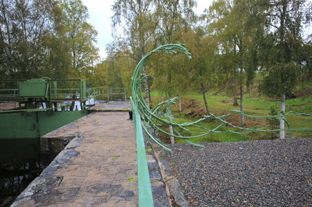 """Kanalparken vid övre slussen i Töcksfors med konstsmidesräcket """"Vågen"""" av konstnären Justus Braunschweig."""