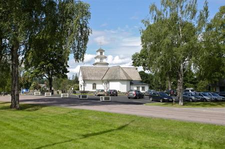 Parkeringen vid kyrkan fylldes med bilar.