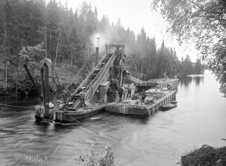 Kanalen vid Kyrkobyn i Östervallskog muddrades för att öka vattendjupet. Efter muddringen var kanalen 1,8 meter djup, vilket var tillräckligt för att den vanligaste typen av lastbåtar skulle kunna gå upp till sjön Östen i Östervallskog. Bilden togs 1912.