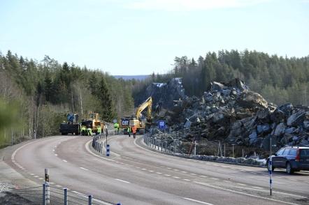 20 februari 2019 - Idag genomfördes den svåraste sprängningen vid tullstationsbygget i Hån. Bergstoppen alldeles intill E18 sprängdes. Det innebar oundvikligen att sprängmassor blockerade E18, med långa bilköer som följd. Två grävmaskiner och två hjullastare samt ett tiotal personer med sopborstar gjorde ett stort jobb för att få igång trafiken.