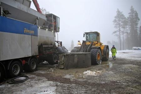 En hjullastare kör betongen i en tunna till gjutplatsen.