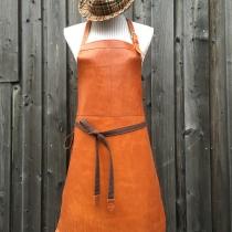 Kock-förkläde i härligt vegetabilgarvat ljusbrunt skinn. Stallbar i nacken med långa knytband i ylletyg. Ögla för slängen.