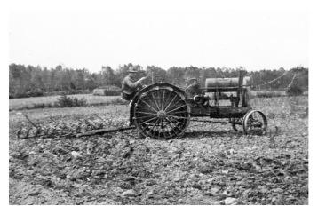 Man på gammal traktor
