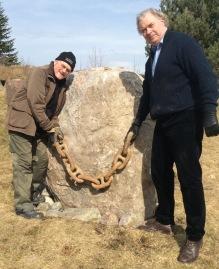 Dicki Sörensen (till vänster) och Mats Wallenius, Svensk-norska samarbetsfonden, under arbetet med minnesstenen våren 2018. Kättingen är drygt 1 meter och väger ca 40 kg. Bild Raija Wallenius.