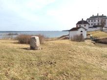 Minnesstenen på sin storslagna plats med slottet i bakgrunden. Ute i vattnet syns även den kobbe där det byggdes en miniatyrfästning under åren 1944- 1945. Bild Mats Wallenius.