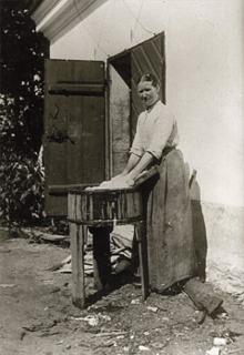 Tvättbyk. Det var ett stort arbete att tvätta. Kvinnan på bilden skrubbar sin tvätt mot ett tvättbräde i sitt tvättkar. Sedan skulle tvätten sköljas flera gånger innan den hängdes upp utomhus.