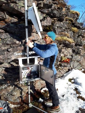 Bild 2: Robin Andersson monterar solpanel för ny avbördningsstation i Tarfala jokken. Fotograf: Torbjörn Karlin.