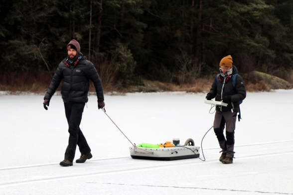 Two master students, Fredrik Andersson and Tobias Möhl, participated in the sampling. Here they are pulling the geo- radar (Malå Geoscience Ramac) equipment over the ice. Photo: Leif Klemedtsson.