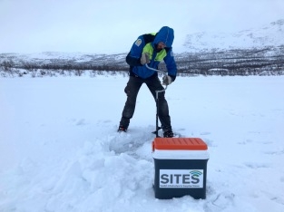 Niklas Rakos drilling a hole in the ice for sampling the lake sediment. Photo: Erik Lundin.