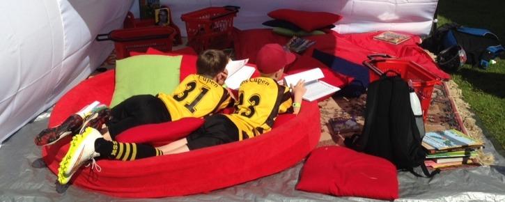 Läsande barn som tar en paus från fotbollen. Med Teamreader på Aroscupen sommaren 2015.