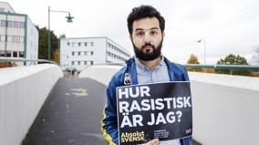"""Soran Ismael i halvbild, håller upp en skylt framför sig där det står """"Hur rasistisk är jag?"""" Han står på en gångbro framför ett förortsområde."""