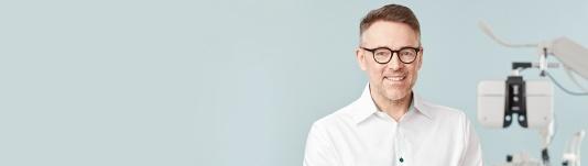 Synundersökning 100 kronor - utan köptvång. ST: En medelålders man med glasögon framför en ögonundersökningsapparat.