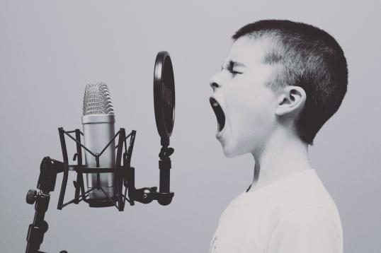 ST: En pojke står framför en mikrofon. Han sjunger med öppen mun och slutna ögon.
