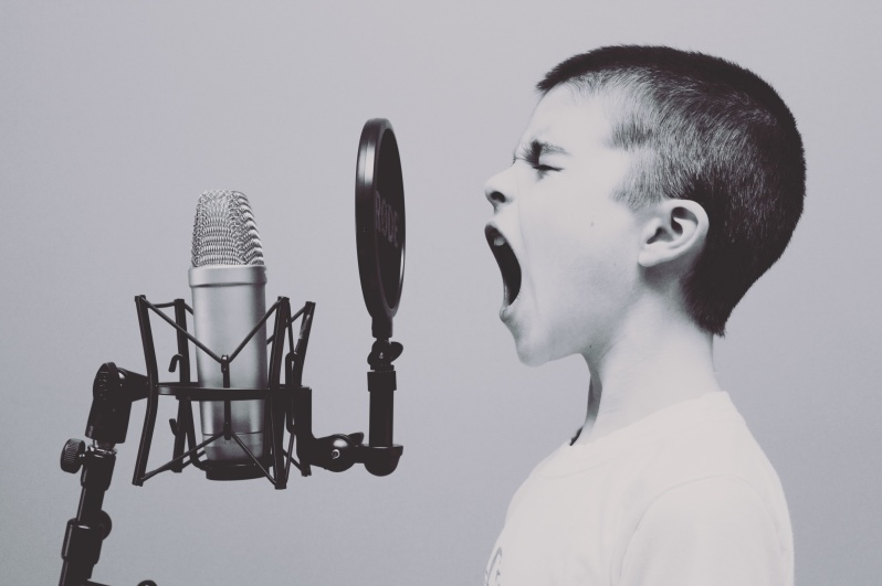 Syntolkning: En pojke står framför en mikrofon. Han sjunger med öppen mun och slutna ögon.