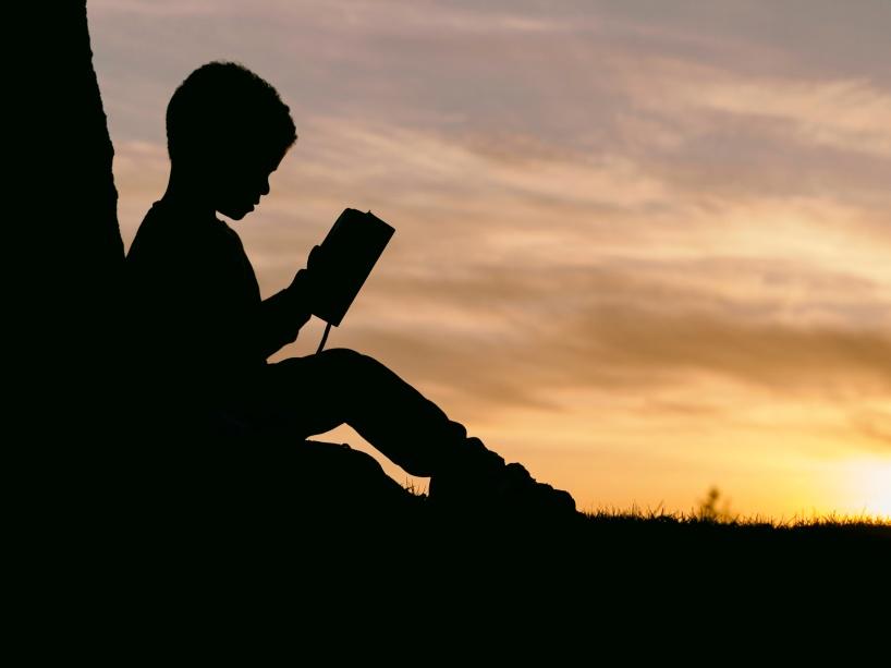 Syntolkning: Ett barn sitter vid ett träd i motljus i solnedgången. Hen läser en bok.