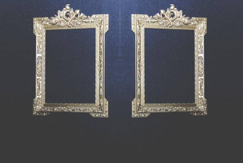 ST: Två tomma ornamenterade guldramar hängda på en svart vägg.