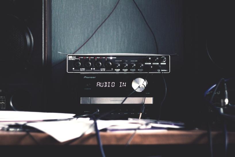 """Syntolkning: Ljudkort och en massa apparater och sladdar på ett bord. På en display står det """"Audio in"""""""