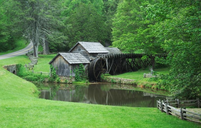 Bildtext: Foto Sam Jotham  från StockSnap. Syntolkning: Ett gammalt hus med vattenhjul vid en damm.  Gräs och träd i olika gröna nyanser omgärdar dammen.